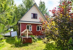 Typical cottage and well on backyard in village Stock Photos