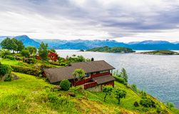 Typical countryside Norwegian landscape with red painted houses. On the shore of the fjord. Cloudy summer morning in Norway, Europe. Artistic picture. Beauty Stock Photos