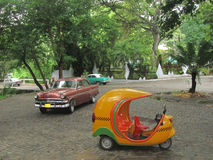 Typical Cuban coco taxi and vintage cars. Cocotaxi is an auto rickshaw type taxi vehicle in Cuba. They have two seats, three wheels, and an egg shaped fibre Stock Photo