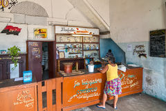 Typical cuban grocery shop. CIENFUEGOS, CUBA - MAY 5: Typical cuban grocery shop with local woman buying something shown on 5 May 2008 in Cienfuegos, Cuba stock image