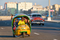 A typical cuban motorbike taxi known as cocotaxi travels along the Malecon seaside avenue in Havana. HAVANA,CUBA - FEBRUARY 24,2017 : A typical cuban motorbike Royalty Free Stock Photo