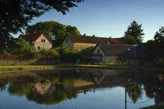 Typical czech small village plaza with pond and trees around. Royalty Free Stock Images