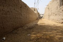 A typical dirt street in one of the larger villages in Tharparkar. Sindh. Houses made of baked clay bricks and mud plaster can be seen on both sides royalty free stock images