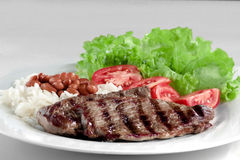 Typical dish of Brazil, rice and beans. This is the most common dish in Brazil, rice, beans, steak and tomato salad with lettuce Royalty Free Stock Photo