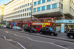 Typical double decker buses in The Strand in London. One of the finest streets in Europe. Royalty Free Stock Images