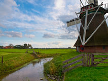 Typical dutch agricultural landscape. With old vintage windmill Stock Image