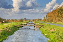 Typical Dutch flat polder landscape with cana and bridges. Typical Dutch flat polder landscape with ponds, Reed belt and canals with old and new bridges against royalty free stock photography