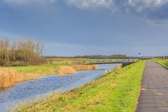 Typical Dutch flat polder landscape with canal and bridge. Typical Dutch flat polder landscape with ponds, Reed belt and canals with old and new bridges against stock photography