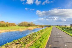 Typical Dutch flat polder landscape. With ponds, Reed belt and canals with old and new bridges against blue sky with scattered clouds royalty free stock photography