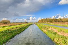 Typical Dutch flat polder landscape. With ponds, Reed belt and canals with old and new bridges against blue sky with scattered clouds royalty free stock images