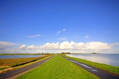Typical dutch landscape. Water, dyke and wideness Stock Photos