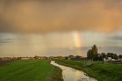 An autumn shower with rainbow in Holland is illuminated by the sun. royalty free stock photography