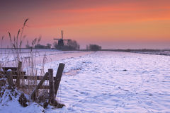 Typical Dutch landscape with windmill in winter at sunrise Stock Images