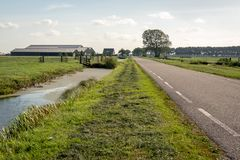 Typical Dutch polder landscape with a country road between the m. Eadows. A farm with barns and stables is visible in the background. The photo was taken at the stock photography