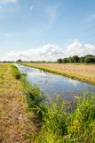 Typical Dutch rural landscape in summertime. Dutch agricultural landscape in the summer season. The cut grass is drying on the field. Diagonally in view is a Stock Photos