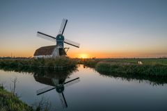 Windmill and decayed house in the dutch countryside near Leiden, Holland at sunset. royalty free stock photos