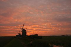 Typical dutch windmills are silhouetted against an orange evening sky royalty free stock photography