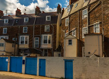 Typical English buildings, red brick buildings, tall wall and bl Stock Image