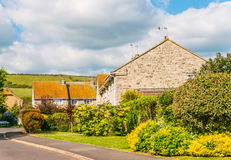 Typical English country house buildings, near the road with sharp bend, greener green, hills in the background. Village royalty free stock photos