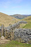 Typical English countryside landscape. English countryside landscape including rocks, hills, grass, drystone wall, taken on a sunny day, Yorkshire Dales, England Royalty Free Stock Images