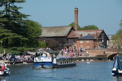 Typical english river scene with large tour boat and factory in background. Crowds of people enjoying the river avon in rowing boats with large trip barge and Royalty Free Stock Photography