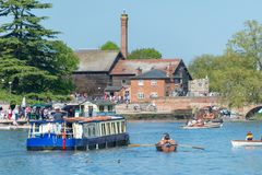 Typical English scene with river traffic in mid summer. Crowds of people enjoying the river avon in rowing boats with large trip boat passing through the middle Royalty Free Stock Image