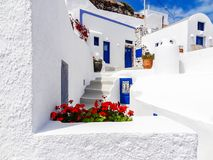 Typical entrance of white houses with blue doors at Santorini Greece. Typical entrance of white houses with blue doors in a sunny Imerofigli, Santorini, Greece royalty free stock images