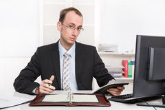 Typical examiner or controller - arrogant and disagreeable sitting at desk with computer