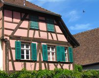 Typical fachwerk house at Riquewihr, Alsace, France. Timbered house with green windows stock photos