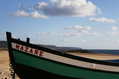 Typical fishingboat from Portugal. Typical fishingboat from the beach of Nazaré - Portugal in the sand with the harbor as background Royalty Free Stock Photography