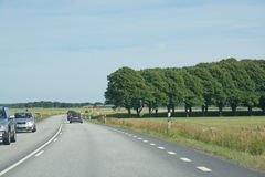 Typical flat landscape South Sweden. AHUS, SOUTH SWEDEN - JUNE 27, 2014: Typical flat landscape in South Sweden from the road in traffic on June 27, 2014 near royalty free stock image