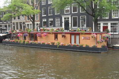 Typical floating house in Amsterdam in the Netherlands. Typical floating house in Amsterdam canals in the Netherlands An emblem of the Netherlands. People live stock images