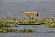 Typical floating house and a fisherman on Inle Lake Stock Image