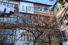 A typical georgian yard of an old traditional wooden house with persimmon tree and clothes and linen drying on the ropes Royalty Free Stock Image
