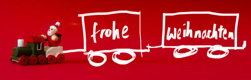 Typical german wooden decoration for Christmas time of a man upo. N a train. Handwritten `Merry Christmas` whishes in igerman language as `Frohe Weihnachten` on royalty free stock photography