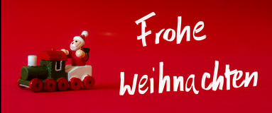 Typical german wooden decoration for Christmas time of a man upo. N a train. Handwritten `Merry Christmas` whishes in igerman language as `Frohe Weihnachten` on royalty free stock photo
