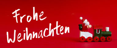 Typical german wooden decoration for Christmas time of a man upo. N a train. Handwritten `Merry Christmas` whishes in igerman language as `Frohe Weihnachten` on stock photo