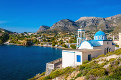 Typical for Greece white church with azure-blue dome. With peacful bay in the background on Kalymnos Island, Greece Stock Images