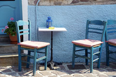 Typical greek cafe scene. Blue chairs and a table in greek taverna Royalty Free Stock Photos