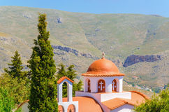 Typical Greek church in mountains with cyprus in the garden, Gre Stock Photography