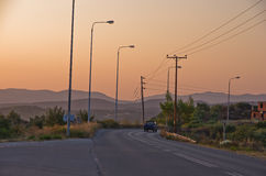 Typical greek coastal road at sunset with one pickup driving by Royalty Free Stock Photos