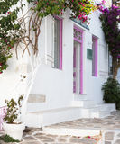 Typical greek house with flowers in the entrance on the cyclades Stock Photos