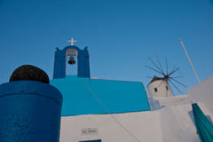 Typical Greek Island Buildings. Buildings, church bell and a windmill in typical colours in Oia, Santorini, Greece Stock Photography