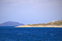 Small greek island on Mediterranean Sea, deep blue water, rocky islet with scant vegetation and some building. Islands near Crete. royalty free stock images