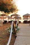 Typical greek scene at the kalives beach with wooden chairs and table royalty free stock photos