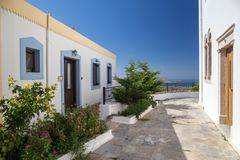 Typical greek street with white buidings and plants. Typical greek street with white houses stock photo