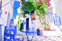 Typical greek traditional village in summer with white walls, blue furniture and colorful bougainvilla, Skiathos Island, Greece. Typical old greek town, narrow royalty free stock photography