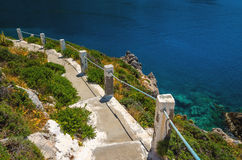 Typical Greek white stairs leading to divers bay on Greek coast. Greece Royalty Free Stock Photo