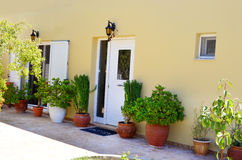 Typical Greek yard of a house  with white doors and  green pot flowers Royalty Free Stock Photos