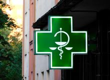 The typical green sign for pharmacies and healtcare related shops. The typical green sign for pharmacies, drugstores and healtcare related shops royalty free stock photos